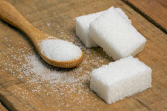 Sugar cube in the spoon on wood background Stock Photography