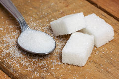 Sugar cube in the spoon on wood background Stock Images