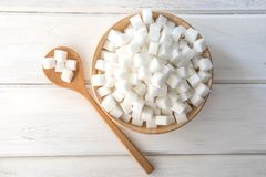 The Sugar cube in wooden bowl on white table , top view and over Royalty Free Stock Image