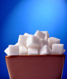 Sugar cubes. Very closeup shot of sugar on bowl against blue Royalty Free Stock Photography
