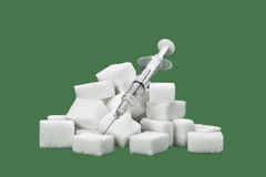 Sugar cubes. With an syringe as a symbol for diabetes Royalty Free Stock Image