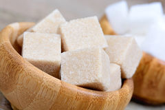 Sugar cubes in a bamboo bowls. On table Stock Photos