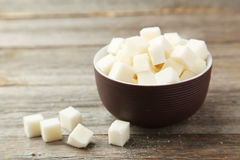 Sugar cubes in bowl. On grey wooden background Royalty Free Stock Photo