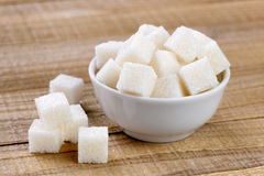 Sugar cubes in bowl. On wooden table Royalty Free Stock Photos