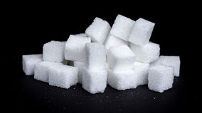 Sugar cubes. In fron of black background Stock Photos