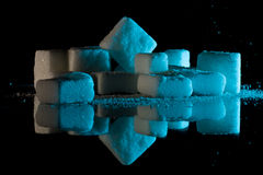 Sugar cubes on glass. A closeup view of sugar cubes and sugar crystals resembling blocks and flakes of snow, arranged on glass with blue lighting, creating a Stock Images
