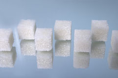 Sugar cubes heap 5. Sugar cubes positioned on glass mirror over blue bakground Stock Photography