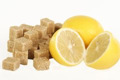 Sugar cubes and lemons. Demerara sugar cubes and lemons on a white background Royalty Free Stock Photography