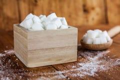 Sugar Cubes no quadrado deu forma à bacia com derramamento do açúcar não refinado sobre no fundo de madeira fotografia de stock