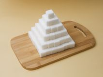 Sugar cubes pyramid. On a yellow basckground Stock Photography