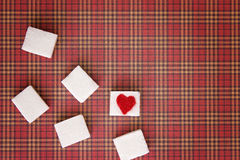 Sugar cubes with a red heart on one of them. Top view. Diet unhealty sweet addiction concept Stock Image