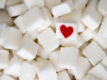 Sugar cubes with a red heart on one of them. Top view. Diet unhealty sweet addiction concept Stock Photography