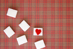 Sugar cubes with a red heart on one of them. Top view. Diet unhealty sweet addiction concept Royalty Free Stock Images