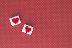 Sugar cubes with a red heart on them. Top view. Sweet addiction valentines day concept Royalty Free Stock Image