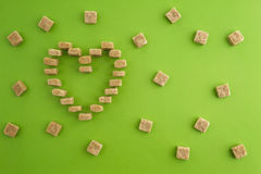 Sugar cubes shaped as heart on greenery background. Top view. Diet unhealty sweet addiction concept Royalty Free Stock Image