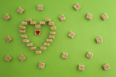 Sugar cubes shaped as heart on greenery background. Top view. Diet unhealty sweet addiction concept Stock Images