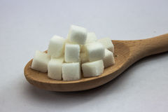 Sugar Cubes on Spoon on Isolated White Background with Harsh Shadow, which can be used to imply dark side of Sugar. Royalty Free Stock Images
