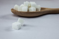 Sugar Cubes on Spoon on Isolated White Background with Harsh Shadow, which can be used to imply dark side of Sugar. Royalty Free Stock Photos