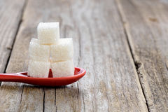 Sugar cubes in spoon. On wooden background Royalty Free Stock Images