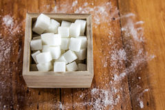 Sugar Cubes in Square Shaped Bowl with Unrefined Sugar spill over in Wooden Background. Royalty Free Stock Photography