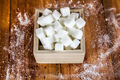 Sugar Cubes in Square Shaped Bowl with Unrefined Sugar spill over in Wooden Background. Stock Image