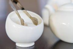 Sugar cubes in sugar bowl and sugar tongs Stock Photos