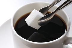 Sugar cubes. Sugar tong clamping a sugar cubes going into the cup coffee Royalty Free Stock Images