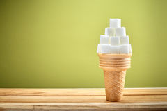 Sugar cubes in wafer cone. On wooden with green background, health and sugar consumption concept Royalty Free Stock Images