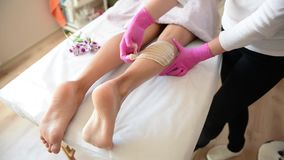 Sugar depilation of the feet in the beauty salon. Rid of hair on the legs