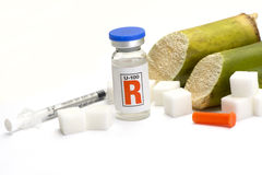 Sugar Diabetes. Sugar cubes, sugarcane, and insulin bottle with syringe Stock Photos