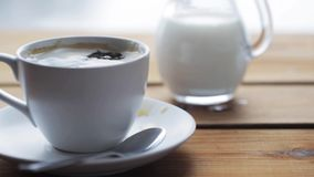 Sugar falling into cup of coffee on wooden table. Unhealthy eating and drinks concept - lump sugar falling into cup of coffee on wooden table stock video footage