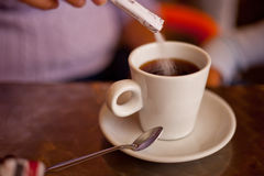 Sugar falling in cup filled with tea Royalty Free Stock Photography