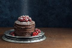 Sugar Falling in polvere sui pancake del cioccolato con le bacche fotografie stock libere da diritti