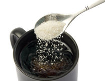 Sugar falling from spoon into a cup. White sugar falling from spoon into a cup isolated on white background Stock Images