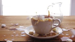 Sugar falling to coffee cup on wooden table. Unhealthy eating, diabetes, object and drinks concept - lump sugar falling to coffee cup and splashing all over stock video
