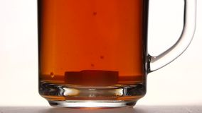 Sugar falls to the bottom of cup tea. Close ups stock video footage