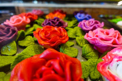 Sugar flowers on candy store. Colored sugar flowers with green leaves Royalty Free Stock Photos