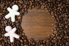 Sugar in the form of little men on coffee beans, space for text Royalty Free Stock Image