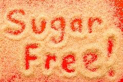 Sugar Free - hand som är skriftlig i partiklar för rått socker på röd backgroun Royaltyfri Bild