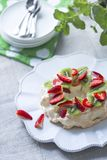 Sugar free pavlova with whipped cream, strawberries and kiwifruit. With mint on a vintage plate stock image