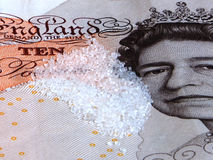 Sugar Grains on £10 note. White sugar grains lying on top of a British ten pound note Royalty Free Stock Photo
