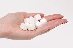 Sugar in hand. Female hand holding pile of white sugar cubes stock photography