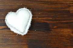 Sugar heart. Heart of granulated sugar on wooden background Royalty Free Stock Photos