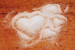 Sugar heart. Heap of white and dark sugar with signs of hearts Stock Photography