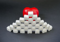 Sugar heart. Heart shape trapped behind a wall made of white sugar cubes, concept for diabetes stock photo