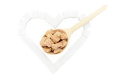 Sugar heart and spoon with brown sugar. The symbol of the heart of the white sugar with a wooden spoon with brown sugar.  on white background Royalty Free Stock Photo