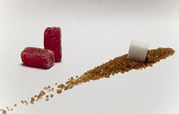 Sugar I. Red candy and white cube over brown sugar Stock Photo