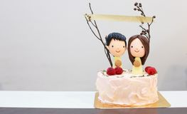 Sugar icing happy smiling couple lovers figure on delicious cake with paper banner on sticks. Birthday Celebration, Anniversary. Happiness concept royalty free stock photography