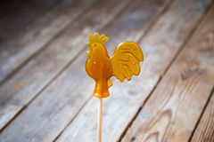 Sugar lollipop rooster on old wood background Stock Image