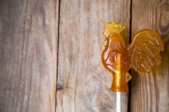 Sugar lollipop rooster on wooden background. Sugar  rooster on wood background Stock Photo